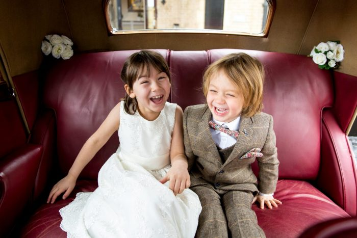 Flower girl and Pageboy having a good giggle in the wedding car at Foxhills Wedding Venue
