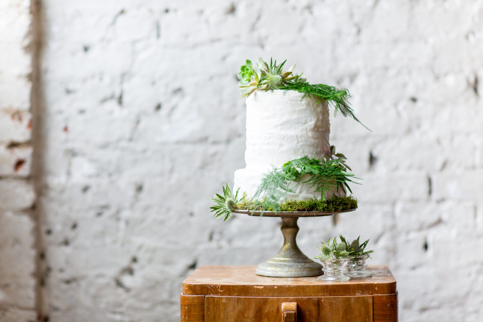 rough iced white wedding cake with natural foliage