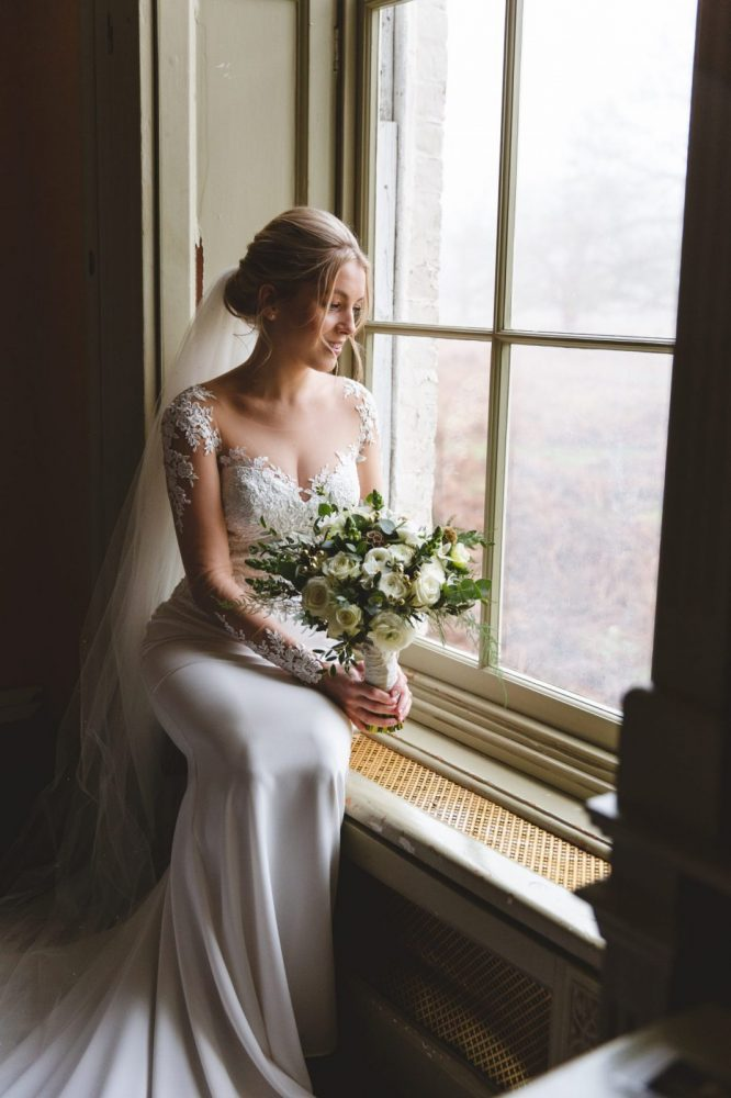 Bride sitting in window with bridal bouquet