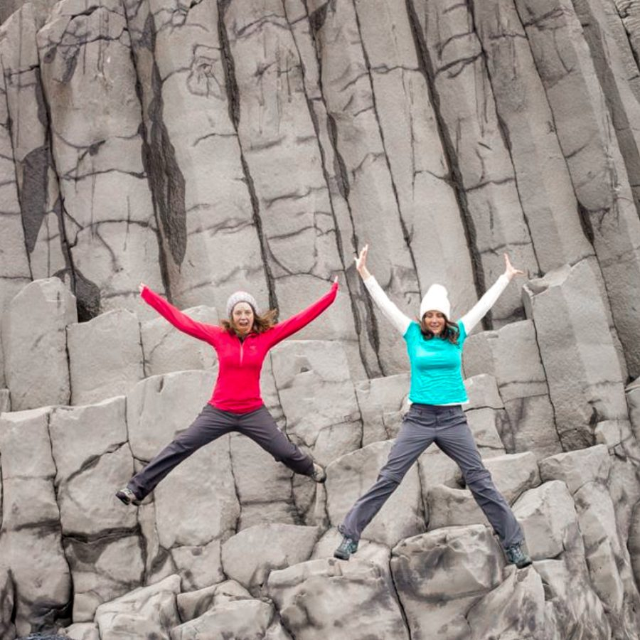 two-girls-jumping-of-rocks-at-vik-beach