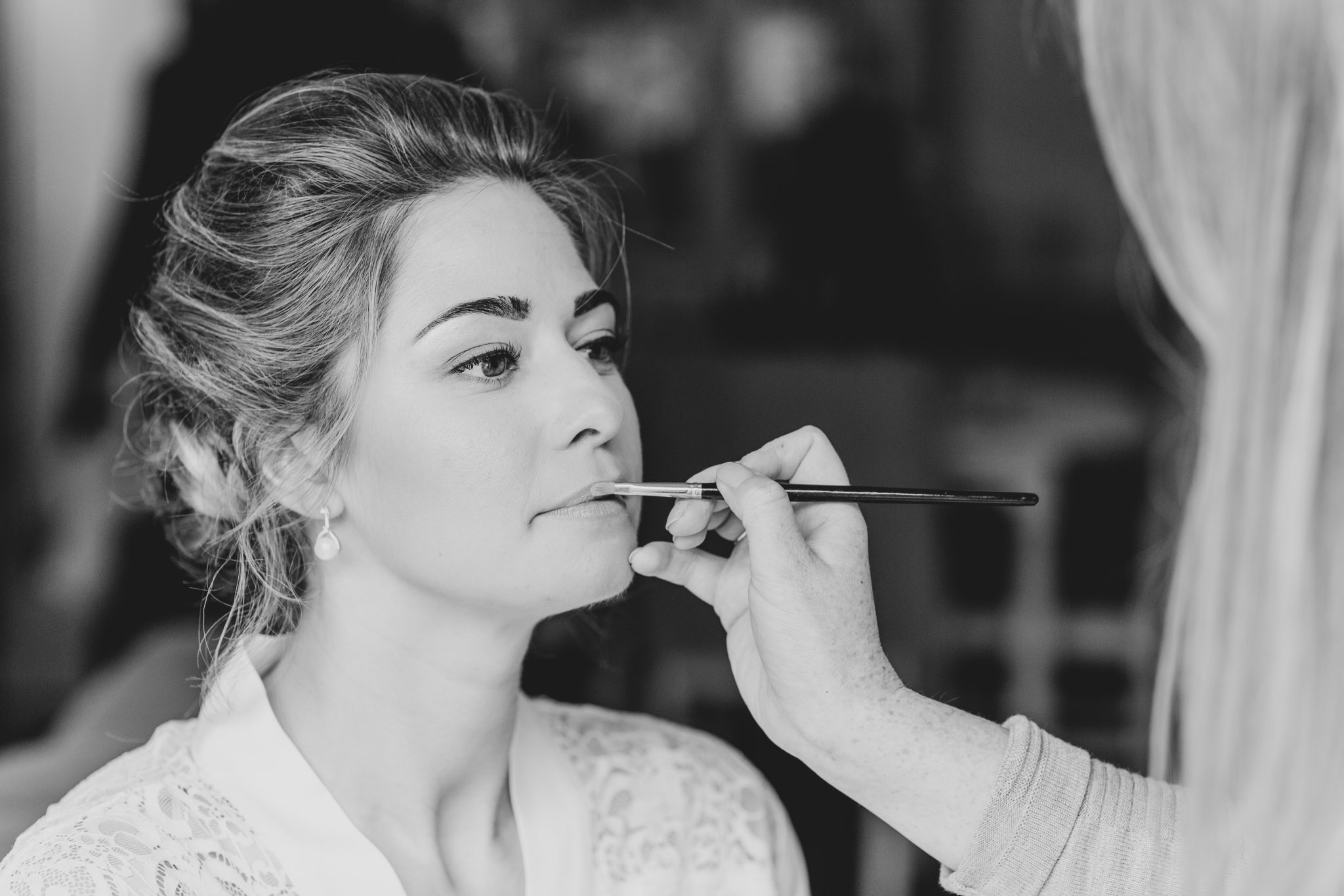 Bride having her makeup done for the wedding