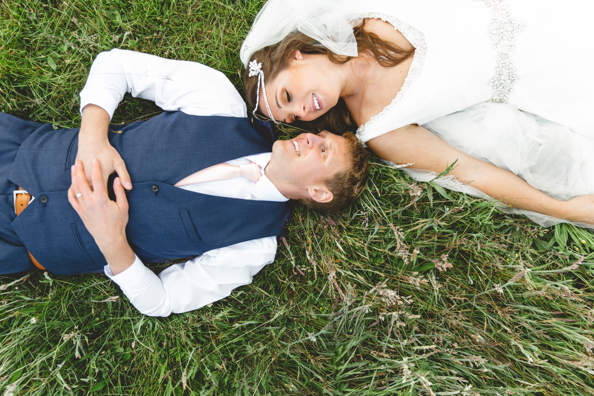 married couple lie in the grass and look into each others eyes
